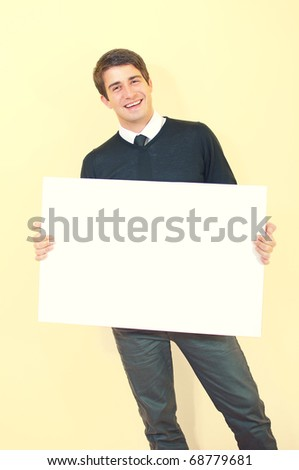 Portrait of a happy attractive young man holding blank white card against uniform background - stock photo