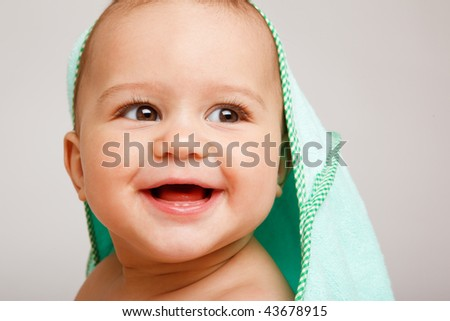 Portrait of a happy baby covered with bath towel - stock photo