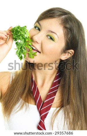 portrait of a happy beautiful brunette girl eating fresh green parsley - stock photo