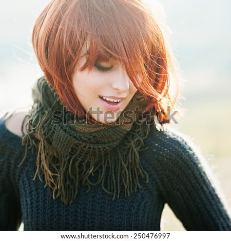 Portrait of a happy beautiful young girl with red hair in the field, lifestyle - stock photo