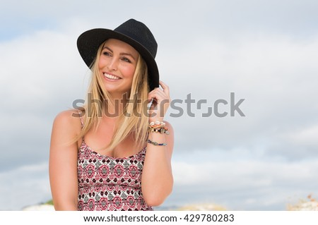 Portrait of a happy blonde woman in casual with a black hat thinking. Serene girl smiling at the beach on a bright sunny day and thinking about her future.  - stock photo