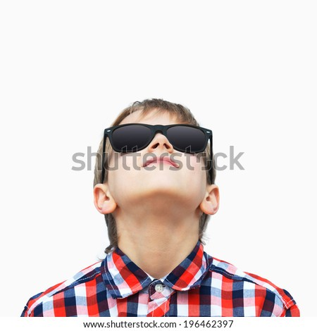 Portrait of a happy boy in sunglasses looking up, white background - stock photo