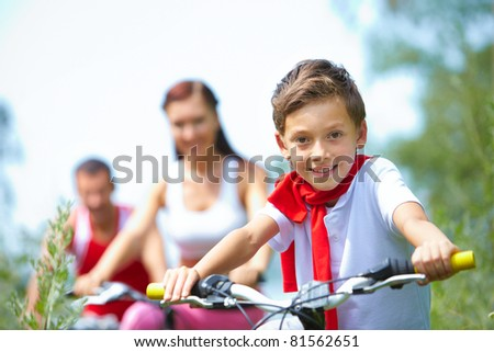 Portrait of a happy boy looking at camera and smiling with his parents in the background - stock photo