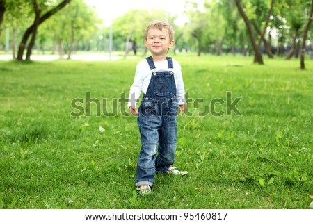 Portrait of a happy boy standing in the park - stock photo