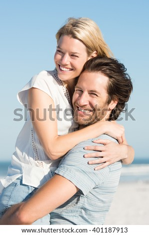 Portrait of a happy boyfriend embracing girlfriend at beach. Handsome man picking up and hugging his girlfriend at sea shore on a sunny day. Young beautiful woman hugging man in love.  - stock photo