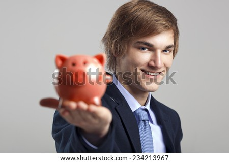 Portrait of a happy businessman holding a piggy bank - stock photo