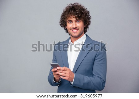 Portrait of a happy businessman holding smartphone and looking at camera over gray background - stock photo