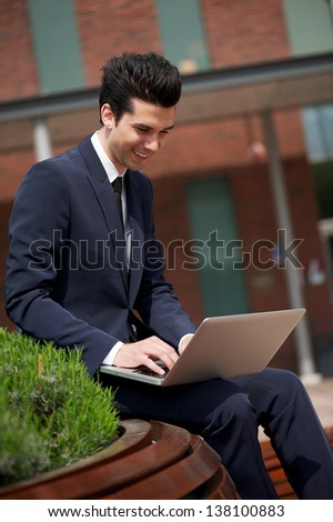 Portrait of a happy businessman sitting outdoors with laptop - stock photo