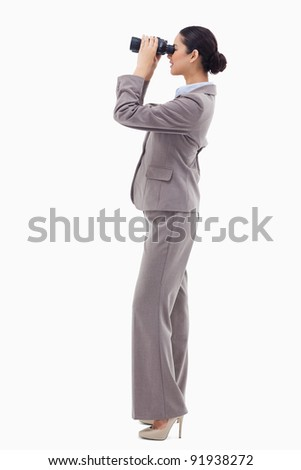 Portrait of a happy businesswoman looking through binoculars against a white background - stock photo