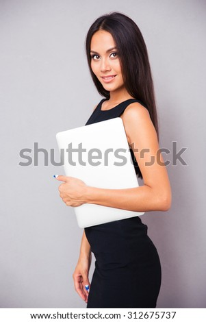 Portrait of a happy businesswoman standing with laptop on gray background - stock photo