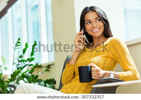 Portrait of a happy businesswoman talking on the phone and holding cup with coffee in office. Looking away - stock photo