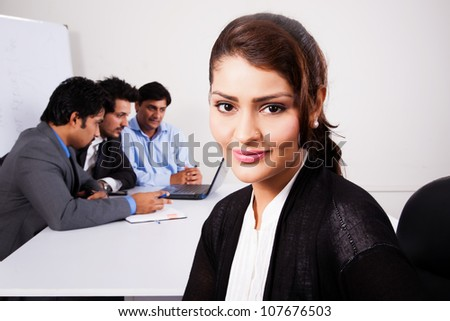 portrait of a happy businesswoman with her colleagues in the background - stock photo
