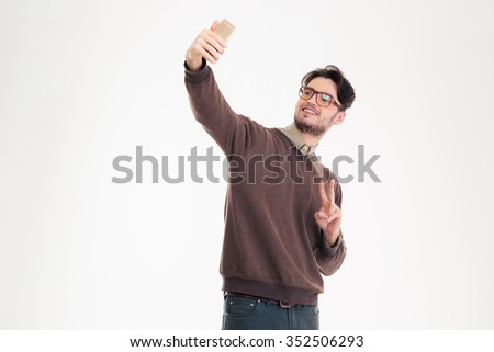 Portrait of a happy casual man making selfie photo on smartphone isolated on a white background - stock photo
