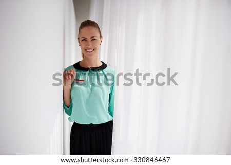 Portrait of a happy charming woman seller posing while standing in modern interior, young female professional worker dressed in corporate clothes enjoying rest after work day and smiling to the camera - stock photo