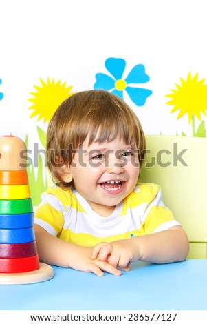 Portrait of a Happy cheerful baby at kindergarten or playgroup, over white background with copy space.  - stock photo