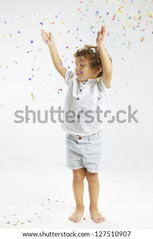 Portrait of a happy child. Beautiful child wrapped with confetti - stock photo
