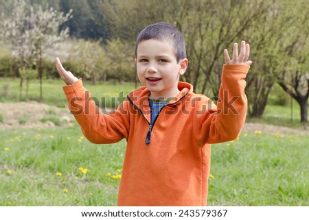 Portrait of a happy child boy in spring garden or orchard. - stock photo