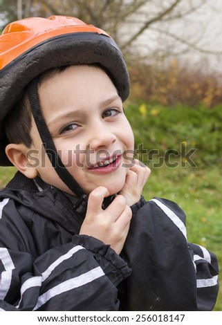 Portrait of a happy  child boy putting on a cycling helmet - stock photo