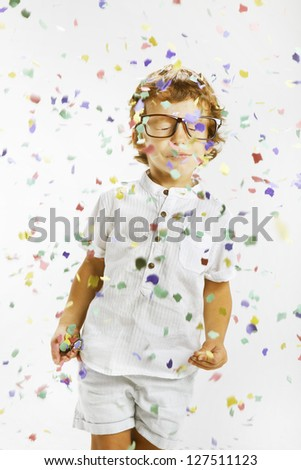 Portrait of a happy child wrapped with confetti. Smiling child with rimmed glasses and confetti - stock photo