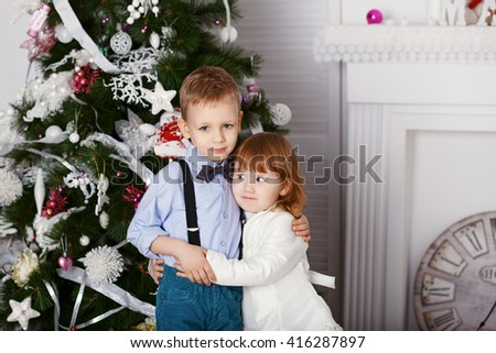 Portrait of a happy children - boy and girl. Little kids in Christmas decorations. Brother and sister hugging. - stock photo