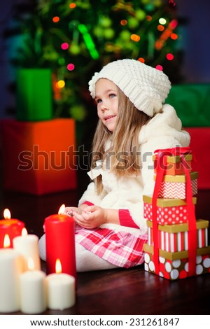 portrait of a happy Christmas toddler girl in white winter hat at lights bokeh background - stock photo