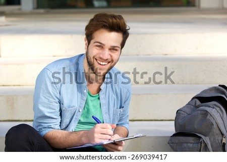 Portrait of a happy college student writing on notepad outside - stock photo
