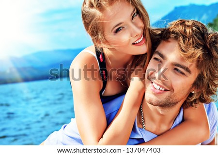 Portrait of a happy couple enjoying vacation on the sea. - stock photo