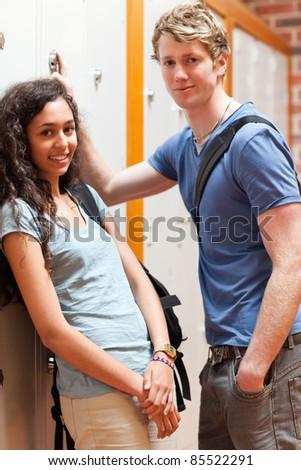 Portrait of a happy couple flirting in a corridor - stock photo