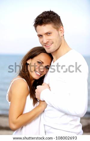 Portrait of a happy couple holding each other's hands posing with the sea as a background - stock photo
