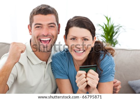 Portrait of a happy couple holding their credit card on the sofa at home - stock photo