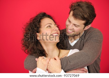 portrait of a happy couple hugging on red background - stock photo