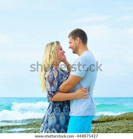 portrait of a happy couple in love on the beach at summer day - stock photo