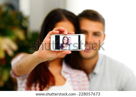 Portrait of a happy couple making selfie photo with smartphone. Focus on smartphone - stock photo