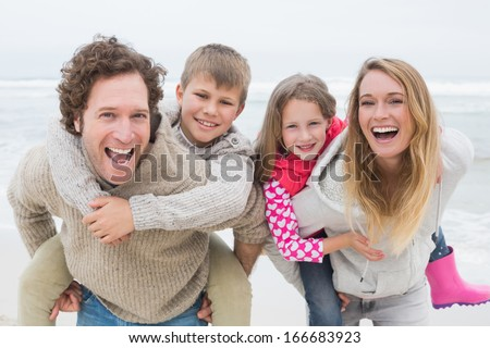 Portrait of a happy couple piggybacking their kids at the beach - stock photo