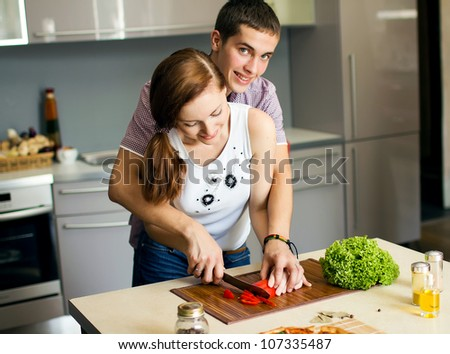 Portrait of a Happy couple preparing food in the kitchen - stock photo