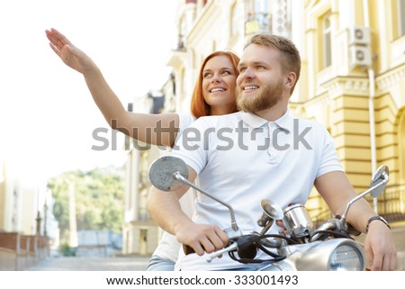 Portrait of a happy couple sitting on a retro scooter while red-haired girl showing something to her handsome bearded boyfriend, both smiling, in a European city - stock photo