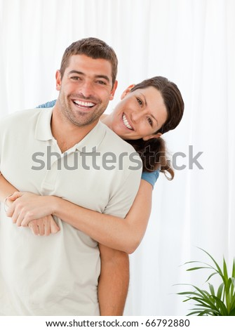 Portrait of a happy couple standing in the living room at home - stock photo
