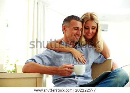 Portrait of a happy couple with coffee, reading the news at home - stock photo
