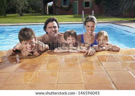 Portrait of a happy couple with three children in swimming pool - stock photo