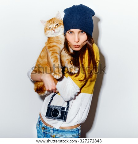 Portrait of a happy crazy hipster girl with camera and ginger cat in a yellow baize and jeans on white background. Retro camera. Hipster girl - stock photo