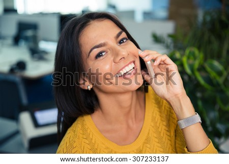 Portrait of a happy cute businesswoman talking on the phone in office - stock photo
