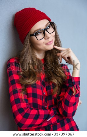 Portrait of a happy cute woman looking at camera over gray background - stock photo