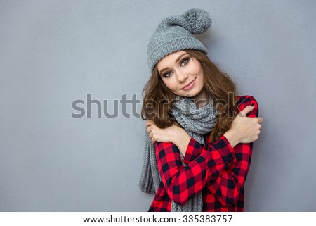 Portrait of a happy cute woman wearing in hat and scarf looking at camera on gray background - stock photo