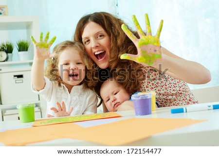 Portrait of a happy family having fun painting with palms and fingers - stock photo
