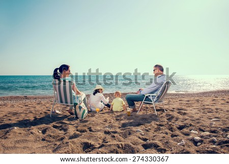 Portrait of a happy family in summer nature. Mother and father are sitting on a beach deck chair, daughter and son playing - stock photo
