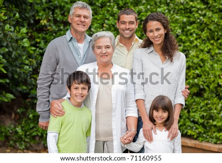 Portrait of a happy family looking at the camera in the garden - stock photo