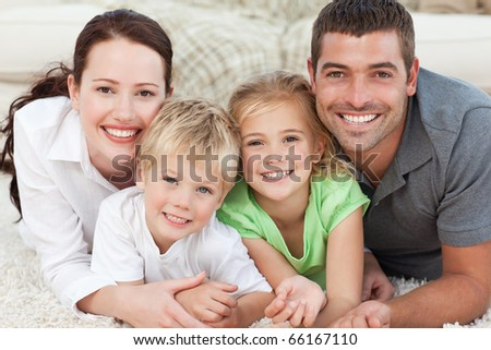 Portrait of a happy family lying on the floor at home - stock photo