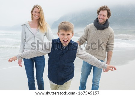 Portrait of a happy family of three walking at the beach - stock photo