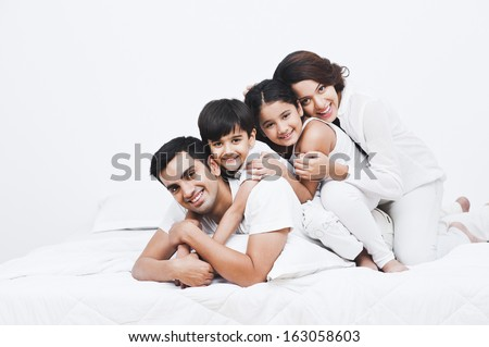 Portrait of a happy family on the bed - stock photo