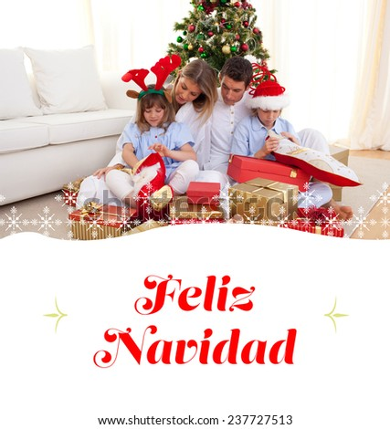 Portrait of a happy family opening Christmas gifts against border - stock photo